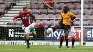 Northampton's Matt Taylor (left) challenges for the ball against Newport