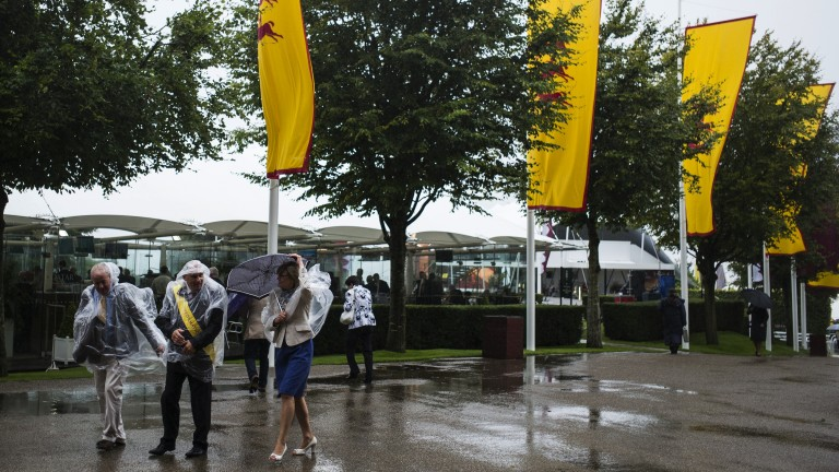 Ponchos on: racegoers are prepared for the rain as they walk around the track