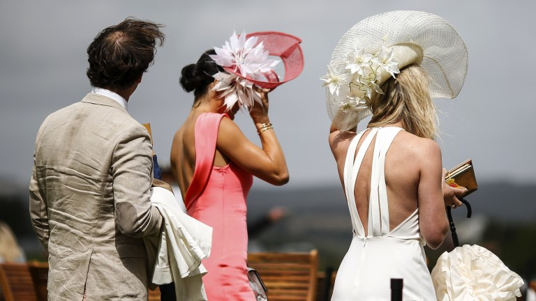 Hold on to your hats: the strong wind causes problems for a couple of racegoers