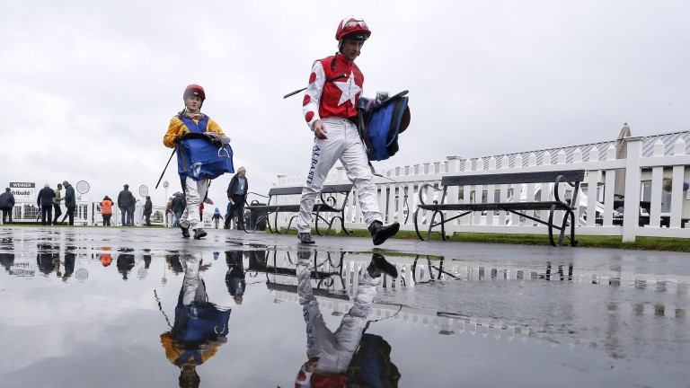 Jockeys return to the weighing room on a wet day at Bath on Wednesday