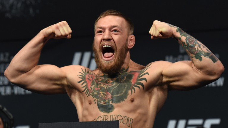 Conor McGregor poses on the scales