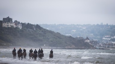 A group of racehorses heading up the beach at Deauville on Monday