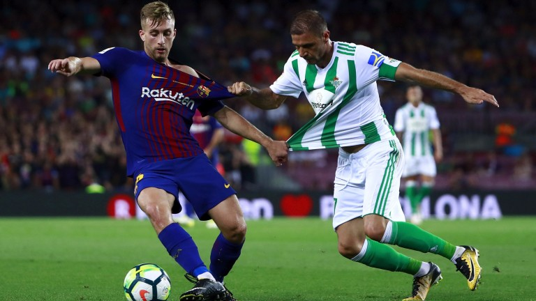 Barcelona's Gerard Deulofeu and Joaquin Sanchez of Real Betis compete for the ball