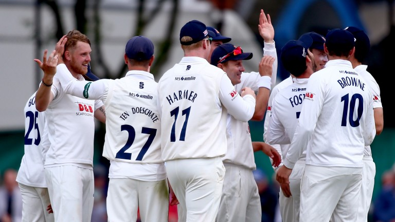 Jamie Porter (left) and his Essex teammates celebrate a wicket against Surrey