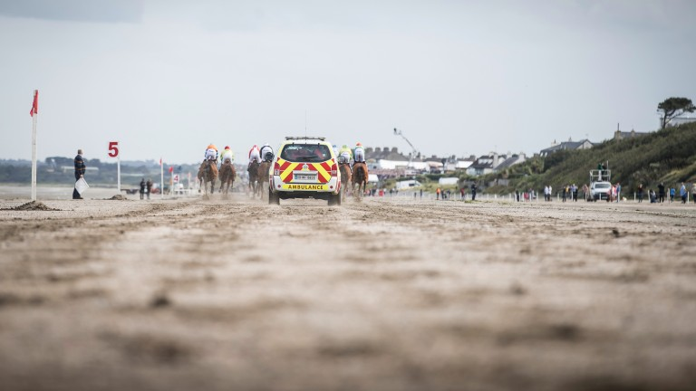 Sand sprinters: the ambulance follows the runners down the beach