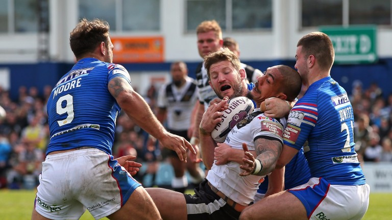Hull's Sika Manu is held up by the Wakefield tacklers