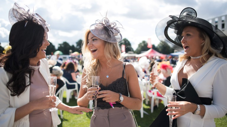 Fun in the sun: racegoers enjoy a glass of bubbly before racing gets under way