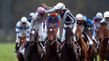 Thierry Gillet (striped sleeves) and Bago are the toast of Longchamp after the 2004 Arc