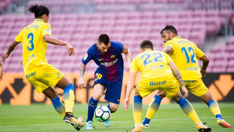 Las Palmas defenders attempt to stop Lionel Messi