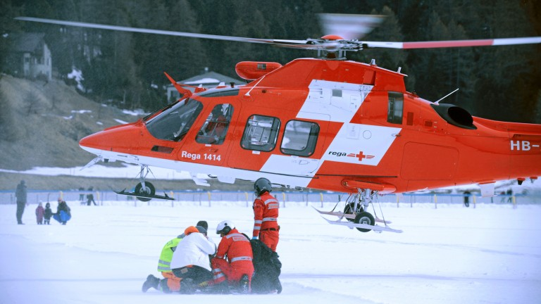 Paramedics attend a stricken George Baker on the frozen lake at St Moritz while a helicopter stands by to airlift him to hospital