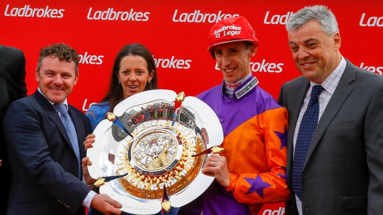 Happy days: George Baker celebrates winning the Ladbrokes St Leger on Harbour Law with trainer Laura Mongan and her husband Ian