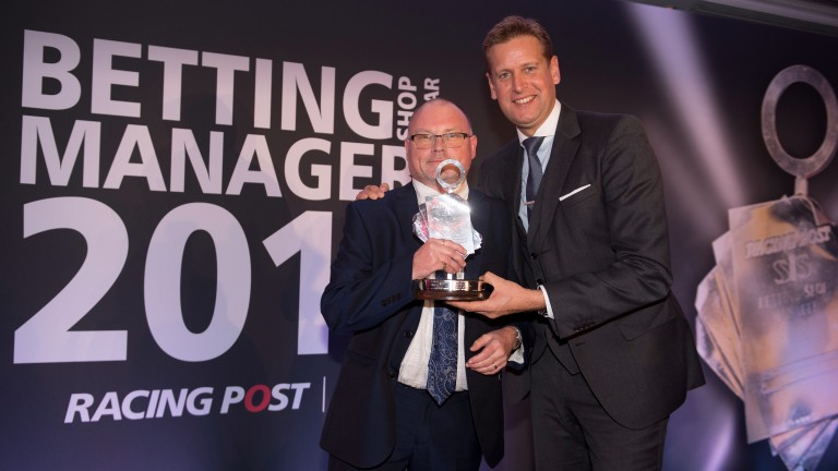 ITV Racing's Ed Chamberlin presents Ron Hearn with his prize after he was crowned Betting Shop Manager of the Year on Monday