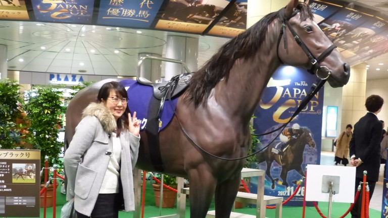 A fan has her photo taken with a model of Kitasan Black at Tokyo's Shiodome station