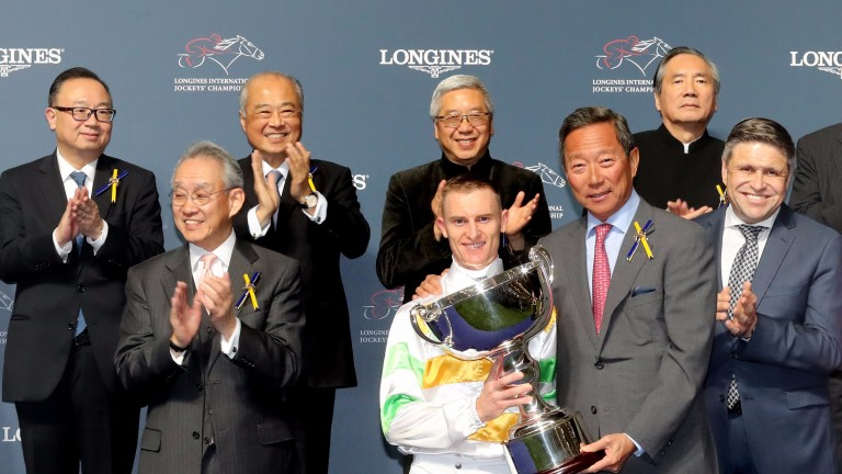 Chairman of the Hong Kong Jockey Club Dr Simon Ip presents Zac Purton with his trophy