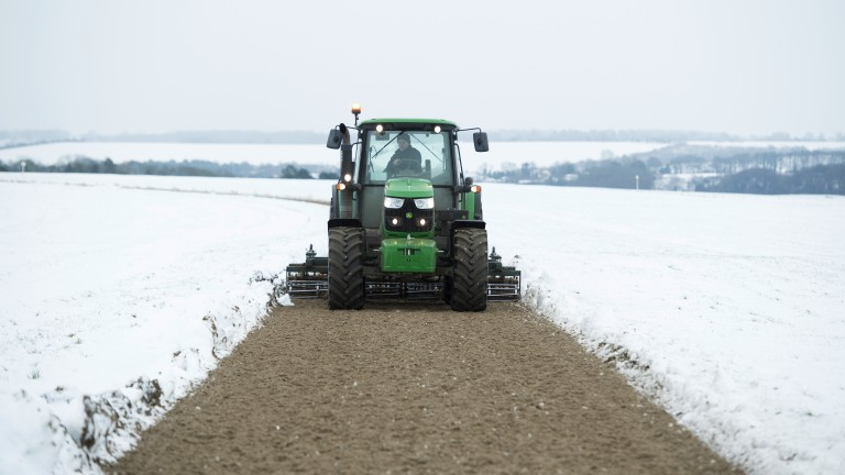 Making tracks: a tractor clears the gallop in Lambourn