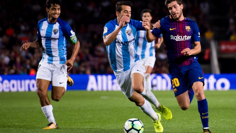 Malaga's Luis Hernandez tussels with Barcelona's Sergi Roberto