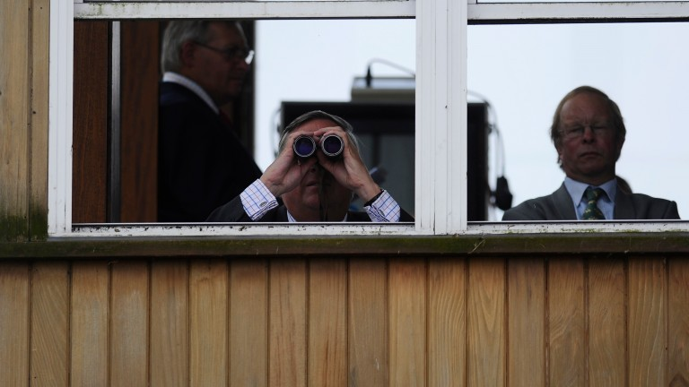 NEWMARKET, ENGLAND - JULY 12: A steward watches the action from the stewards box at Newmarket racecourse on July 12, 2014 in Newmarket, England. (Photo by Alan Crowhurst/Getty Images)