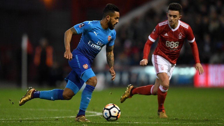 Theo Walcott carries the ball past Zach Clough of Nottingham Forest