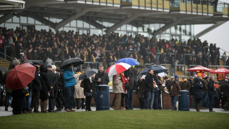 Umbrellas up: racegoers follow the action on the track