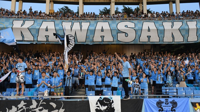 Supporters of Kawasaki Frontale cheer their team at Todoroki Stadium