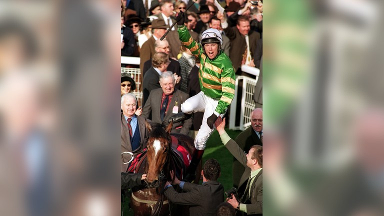 Charlie Swan performs a rare jump jockey flying dismount following the second of Istabraq's three Champion Hurdle victories