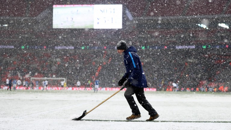 Ground staff clear the pitch of snow during Tottenham v Rochdale at Wembley