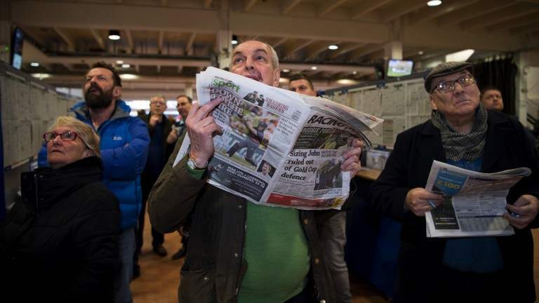 Follow your fancy: a punter watches a race unfold while gripping his Racing Post