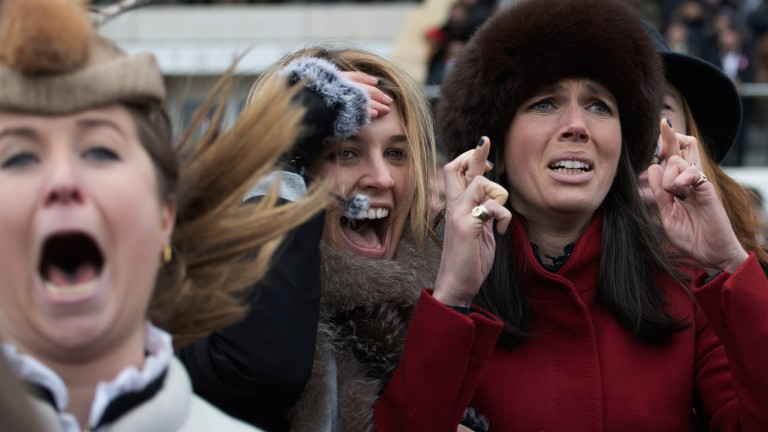 Fingers crossed: racegoers watch the finish to the Champion Chase with interest