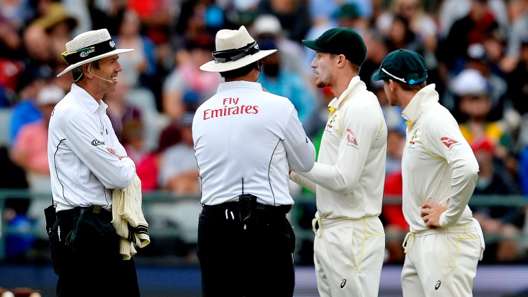 The umpires confront Australia's Cameron Bancroft and Steven Smith in Cape Town