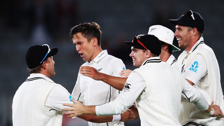 Trent Boult (second left) celebrates one of his nine wickets in Auckland