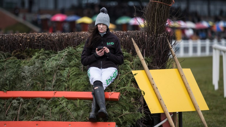 Sitting on the fence: Rachael Blackmore catches up on her phone from an unusual spot before racing