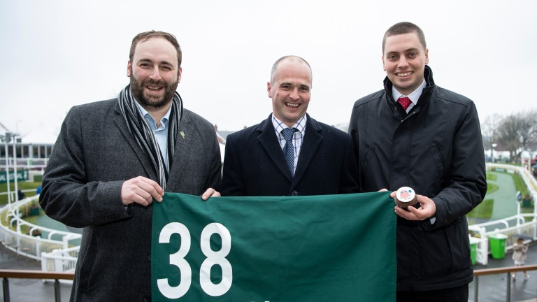 Competition winner Andrew George (left) and his brother Daniel (right) flank trainer David Dennis at Aintree