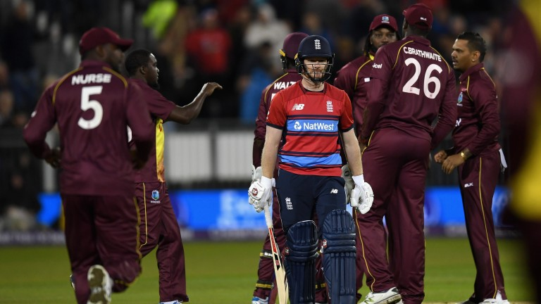 West Indies players help Sunil Narine celebrate the wicket of England captain Eoin Morgan