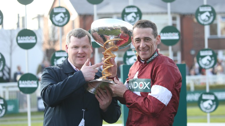 All smiles: Jockey Davy Russell and trainer Gordon Elliott lift the Grand National trophy after Tiger Roll's win