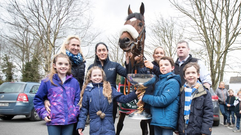 Tianna and Matt O'Leary grasp the Grand National trophy as mum Anita (second left) and their brother Zack (right) and cousin Ava (left) look on. Gordon Elliott (top right) is joined by staff Karen Morgan (left of horse) and Louise Dunne (right of horse)