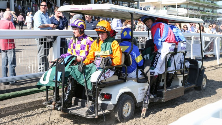 Jockeys are transported back to the weighing room after the third race at Cheltenham, where temperatures hit 25C