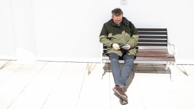 Mark Johnston takes advantage of a quiet moment at Epsom to study form