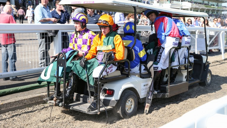 Jockeys are ferried back to the weighing room on a red-hot day at Cheltenham this year