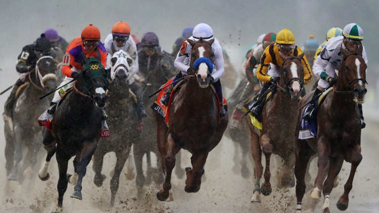 Justify (blue noseband, middle) sits just outside leader Promises Fulfilled (right) as the field heads into the first turn in the Kentucky Derby
