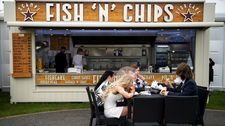 Tucking in: racegoers sit down for lunch before the start of racing