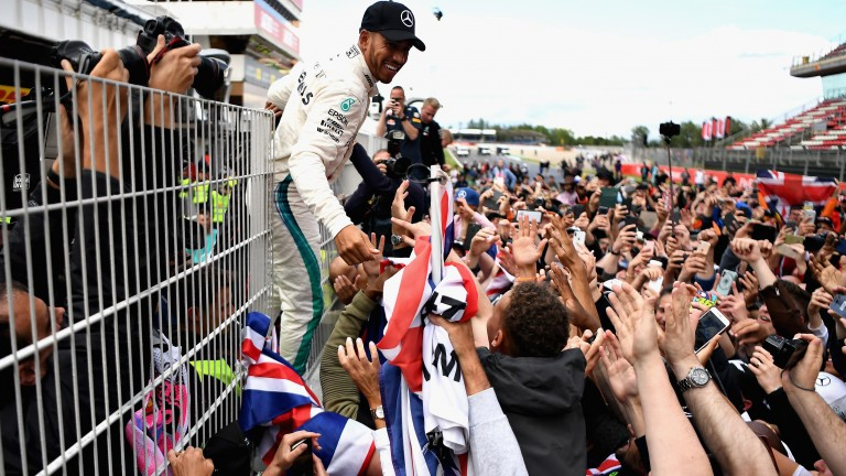 Lewis Hamilton celebrates with his fans on the pit wall after the Spanish Grand Prix