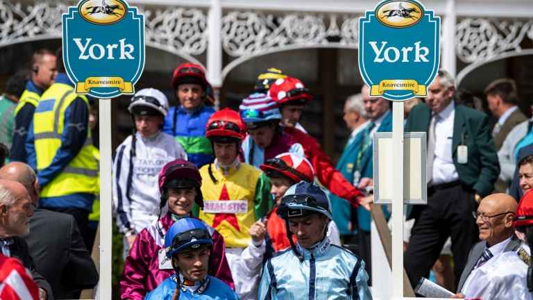 Colourful characters: jockeys walk into the paddock for the first race at York