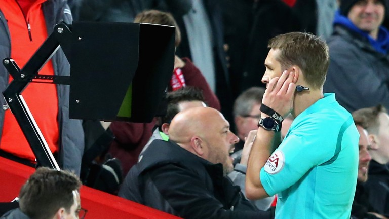 Referee Craig Pawson watches the VAR screen during Liverpool v West Brom