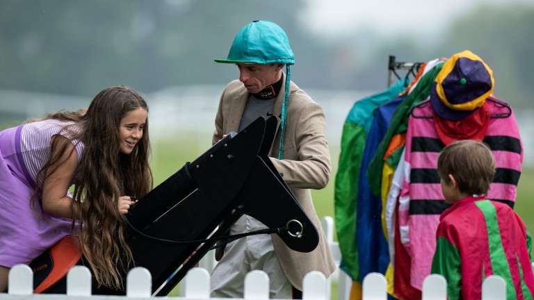 Fun and games: Dave Crosse shows some young racegoers how the horse exerciser works