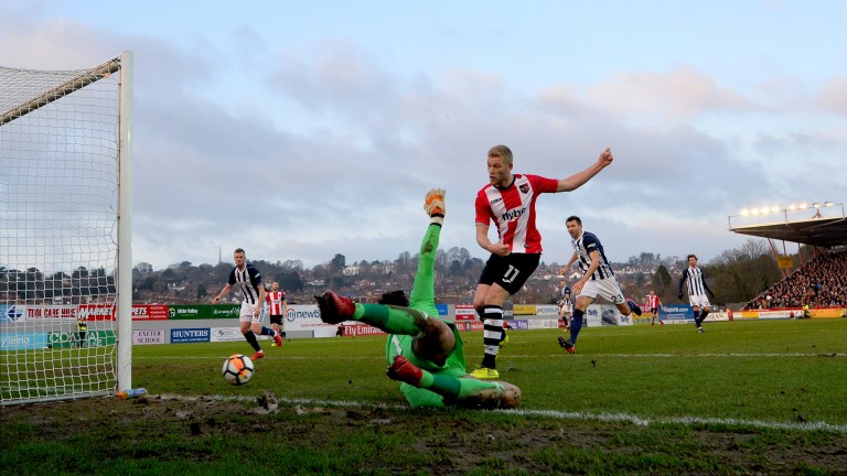 Jayden Stockley of Exeter takes a shot against West Brom