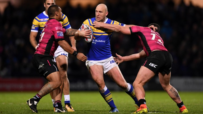 Carl Ablett of Leeds is tackled by Sika Manu and Mark Minichiello of Hull