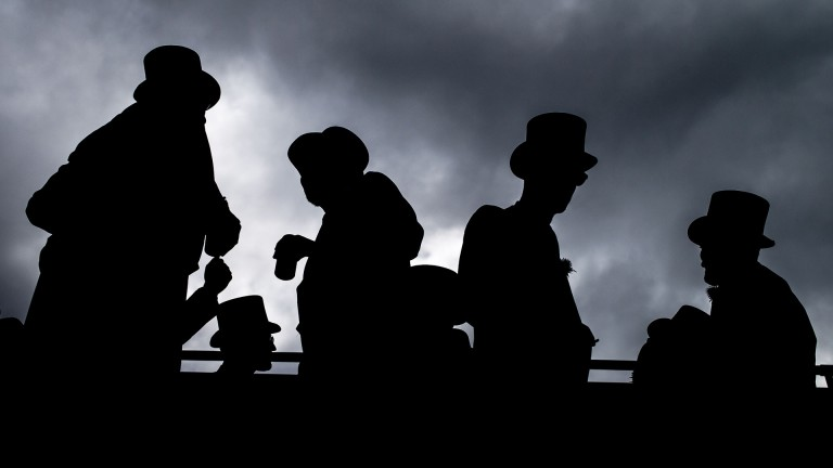 Get the top hats out: racegoers in their morning suits share a drink as they arrive on the Downs