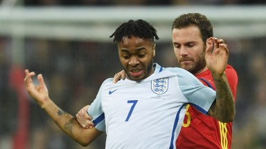 Raheem Sterling of England holds off Spain's Juan Mata