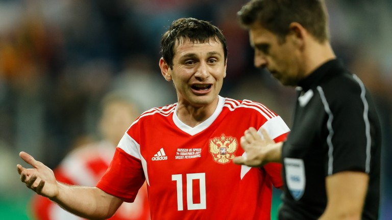 Russia's Alan Dzagoev argues with the referee