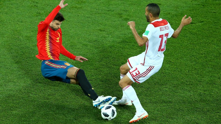 Spain's Gerard Pique lunges in on Khalid Boutaib of Morocco